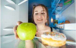 a woman putting an apple and donut into her refrigerator, Refrigeration 101: Understanding the Working of a Refrigerator