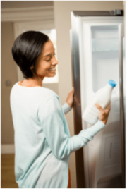 a woman holding a bottle of milk, standing in front of the refrigerator, Your Fridge is Freezing Everything – What's Going On