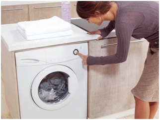 a house wife operating her front load washing machine, check out these simple front load washing machine maintenance tips